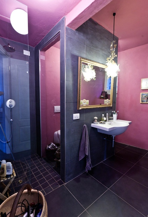 a bold mauve and purple bathroom with various types of tiles, elegant lighting and a gallery wall