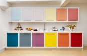 a contemporary rainbow kitchen with cabinets done in bold mismatching shades and uppers in more muted shades looks just jaw-dropping