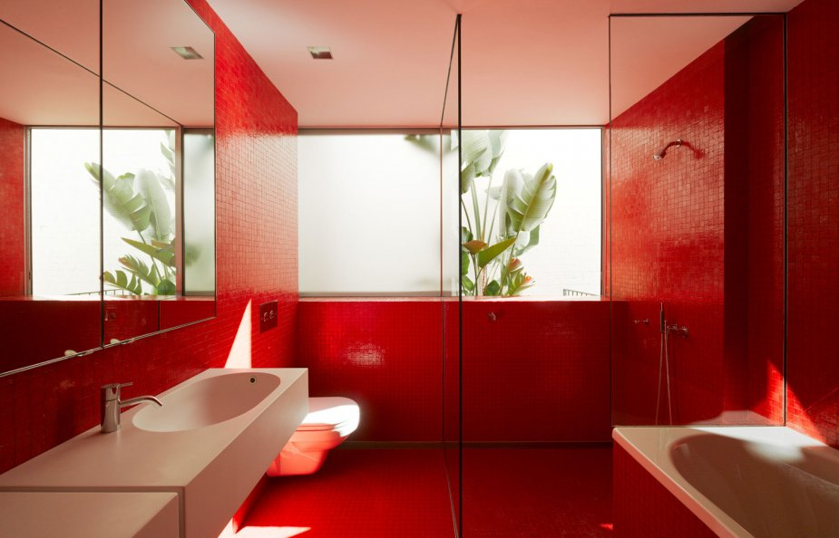 a minimalist red bathroom done with a large window and white appliances   a sink and a tub
