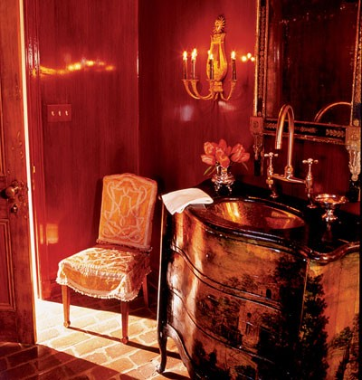 a refined red and gold bathroom with a vintage feel, a chic vanity, a wall sconce and a vintage chair