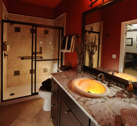 a modern bathroom with burgundy walls, with neutral stone and neutral tiles in the shower and some lights