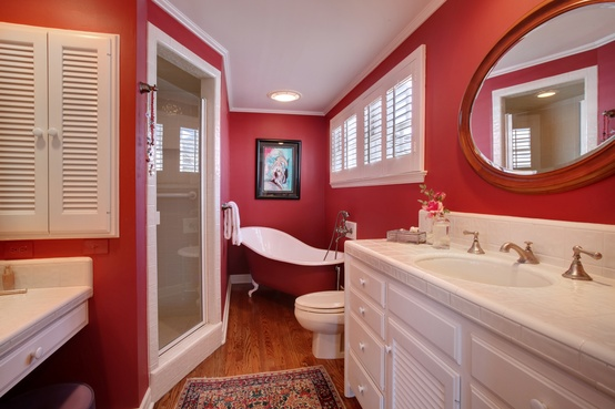 a small red bathroom with whites to refresh   a red and white bathtub, a white vanity and sinks plus a white shower space