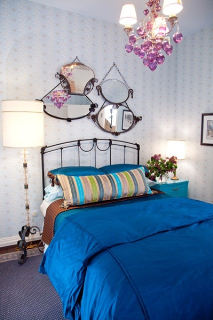 A bunch of mirrors add  above the bed creates lots of dimension in this space.
