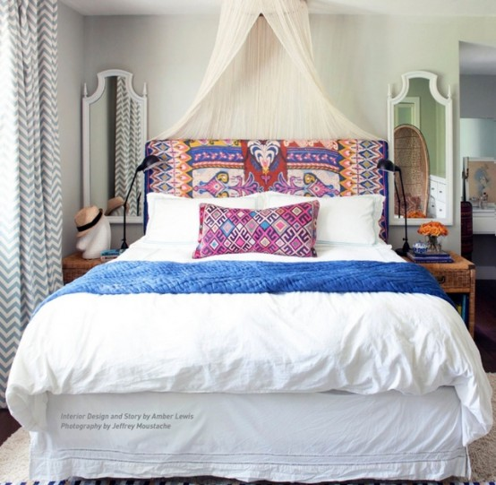 Bright boho color palette should always come with something soft and neutral. White sheets, walls and a canopy looks well with such textile headboard and throw pillows.