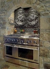 a light-colored Gothic kitchen of light stone, a vintage backsplash and lights over the cooker