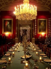 a sophisticated Gothic dining space with red walls, a jaw-dropping chandelier, a long table with candles and refined artworks