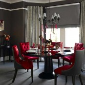 a sophisticated Gothic dining space wiht a black round table, red upholstered chairs, a vintage chandelier and red candles and glasses