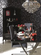 a modern Gothic dining room with skull wallpaper, a glass table, grey leather chairs, a glass armoire and a beautiful and shiny chandelier