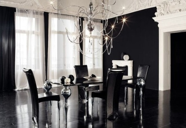 a refined modern black and white dining space with a ling table on catchy legs, black chairs, black curtains and walls, a catchy crystal chandelier