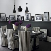 a modern Gothic dining room with black half walls, a black table, striped chairs, pendant black lamps and a gallery wall on the ledges