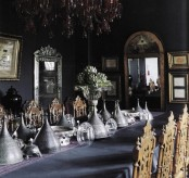 a beautiful and moody Gothic dining room with black walls, a gorgeous red chandelier, mirrors and artworks, a long table with cones and carved wooden chairs
