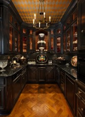a moody Gothic kitchen in black, with vintage cabinets, a vintage chandelier, a bold geometric ceiling and vintage plates and bowls