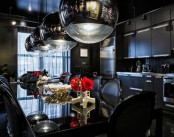 a modern Gothic eat-in kitchen with sleek black cabinetry, a black backsplash, a black glass table and leather chairs, catchy bubble lamps and bone vases