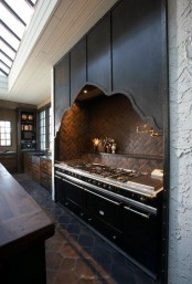 a dramatic Gothic kitchen in dark shades, with an oversized black cooker with a stone backsplash and a built-in catchy hood over the cooker
