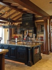 a Gothic kitchen with heavy wooden cabinets and a dark wooden kitchen island, a large vintage hood and a beautiful chandelier over the island