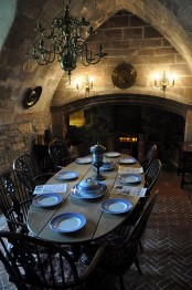 a refined vintage Gothic kitchen with stone walls, a fireplace, an oval table and vintage chairs plus a chic chandelier