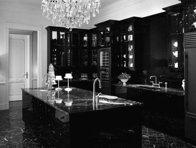a fantastic black Gothic kitchen with modern cabinets, refined black marble countertops and a large crystal chandelier