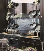 a chic dark kitchen with modern moody cabinetry, a shiny tile backsplash and a metal hood is a chic idea