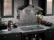 a modern and refined Gothic kitchen with dark cabinets, a metallic backsplash and stone countertops is lovely