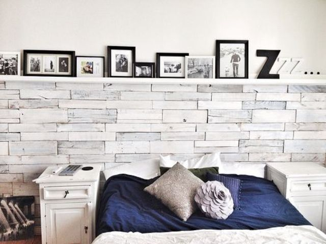 a modern rustic bedroom with a whitewashed wooden wall, white nightstands, a ledge with lots of artworks and contrasting bedding
