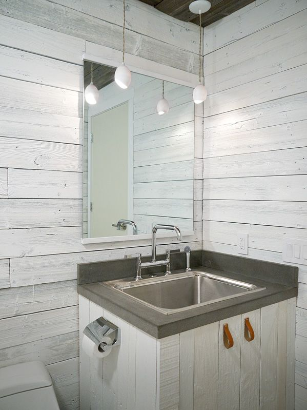 a farmhouse bathroom done with whitewashed wood, with pendant lamps, a whitewashed vanity and a metal sink plus a mirror with no frame