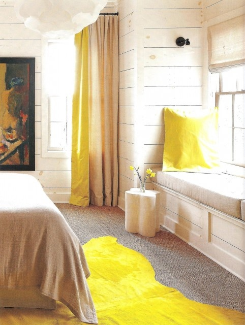 a bright farmhouse bedroom with whitewashed walls, neutral furniture and bright yellow accents plus an artwork is wow