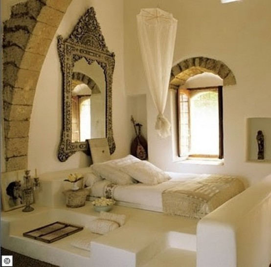 a creamy Moroccan bedroom with a zen feel, with a bed on the floor, some seats, lovely accessories and a vintage framed mirror and a canopy over the bed