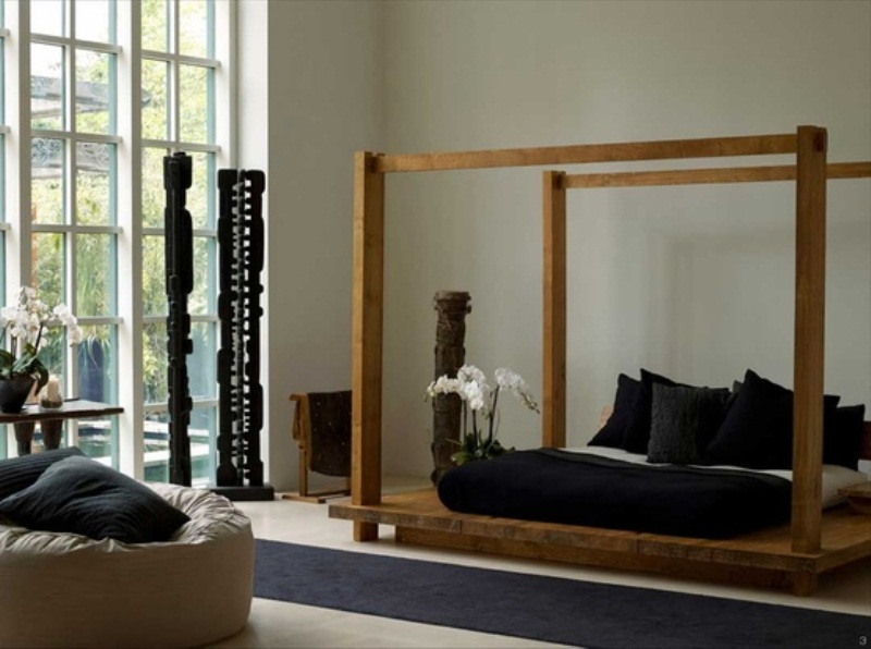 an Asian bedroom with a strong zen feel, with a wooden bed and black bedding, a neutral chair and black carved pillars as decor