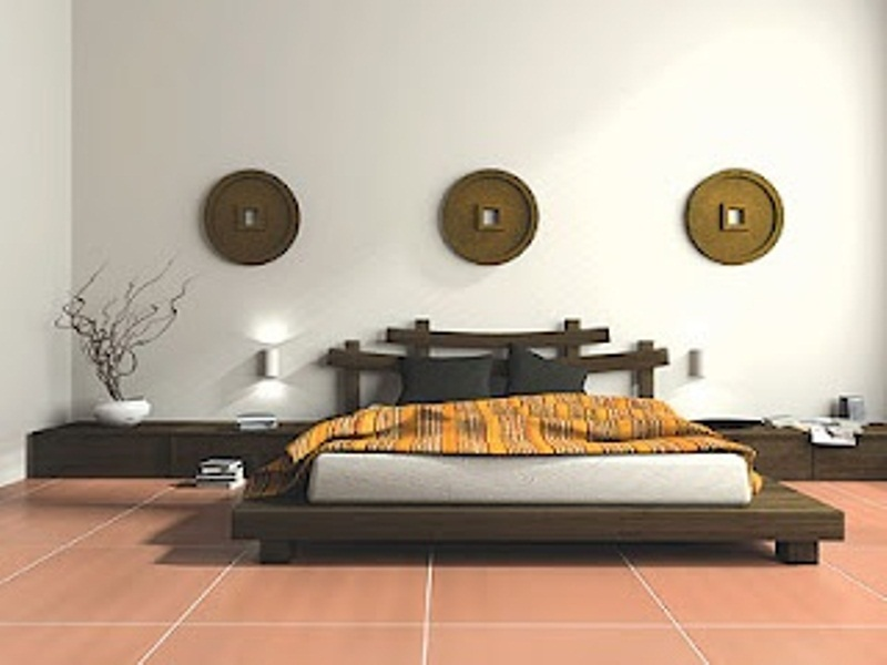 a zen inspired Asian bedroom with low wooden furniture in Asian style, neutral bedding, branches and decorative plates on the wall