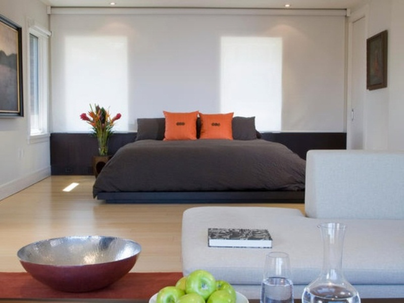 a modern zen bedroom with a dark bed and dark bedding, some statement artworks and a creamy sofa, a low table and drinks