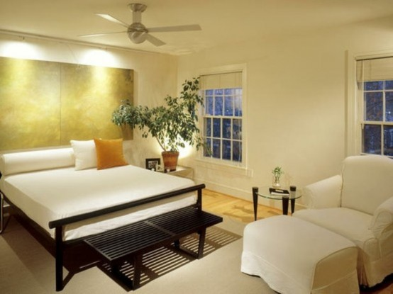 a neutral zen-like bedroom with a polished gold accent wall, a black bed with white bedding, a white chair and soem statement plants