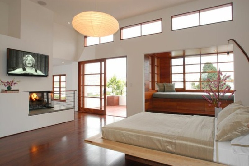 a neutral Japanese style zen bedroom with a wooden bed, a daybed by the windowsill, a built in fireplace and paper lamps