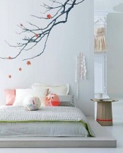 a romantic Japanese bedroom with a platform bed, pillows and blankets, a blooming branch on the wall and a pretty wooden nightstand