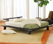 a neutral zen bedroom with a low black bed, a black leather chair, green and white bedding and a statement plant
