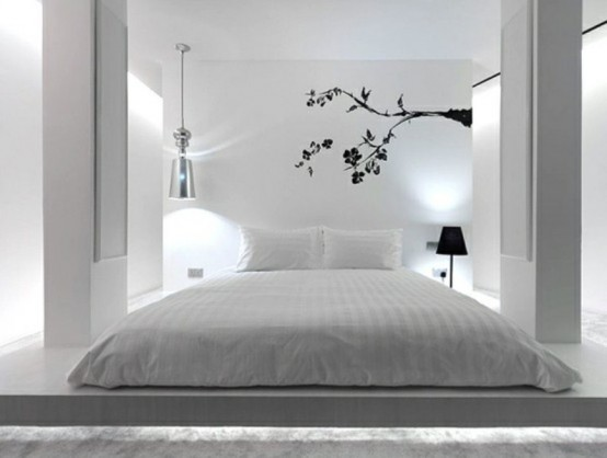 a pure white bedroom with a bed on the floor, pillars, a pendant and a floor lamp and a black blooming branch decal on the wall