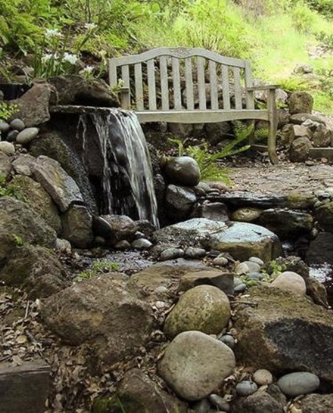 Don't forget to put a bench near your backyard waterfall. You'll definitely enjoy the sound of falling water while relaxing on it.
