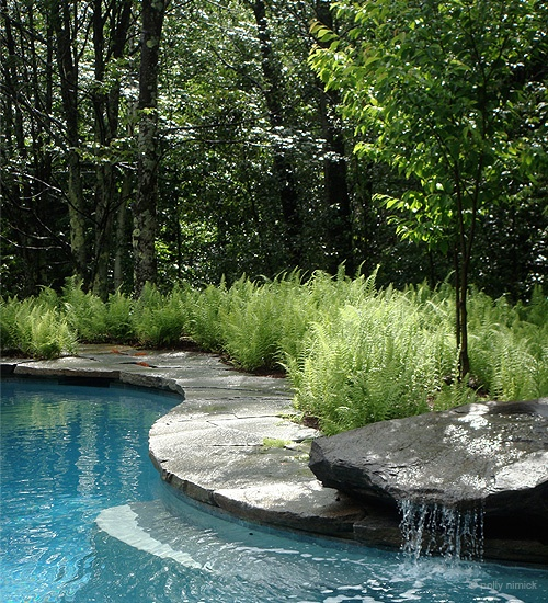 One large rock is more than enough for a beautiful waterfall by the pool.