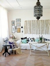 a neutral Moroccan living room with traditional lamps and a Moroccna wedding blanket on the wall