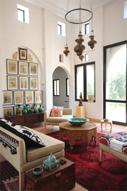 a beautiful Moroccan living room with pendant lamps, modern furniture and carved tables plus patterned textiles