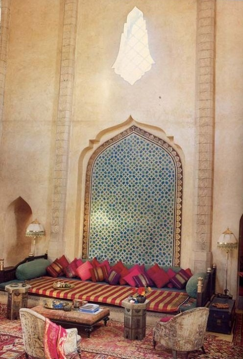 a bright Moroccan living room with colorful pillows and cushions, rugs and mosaics on the wall