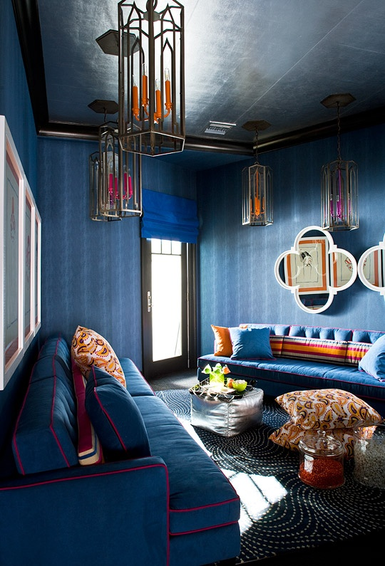 a bold blue living room done with pendant lamps and colorful pillows for an accent