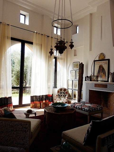a neutral Moroccan living room spruced up with carved furniture, a cluster of pendant lamps and a mosaic fireplace