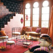 a super colorful living room with wrought furniture, bright textiles and colorful pendant lamps