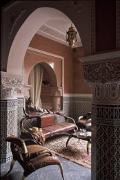 a Moroccan living room done in muted tones, with mosaic tile walls, traditional lanterns and carved furniture