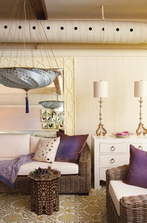 a neutral Moroccan living room spurced up with purple touches, carved and painted tables and pendant lamps