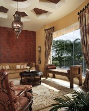 a muted tone Moroccan living room with an embellished pendant lamp, luxurious textiles and carved furniture