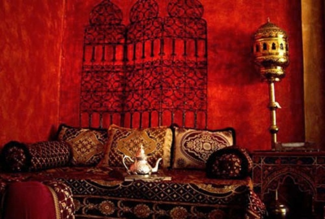 a hot red Moroccan living room with an orante screen on the wall, a bright sofa with pillows and a cool floor lamp