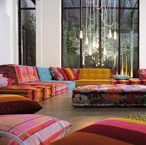 a colorful Moroccan living room with bold and patterned sofas and cushions plus pillows