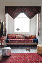 a neutral nook with a built-in sofa, colorful and patterned textiles and leather ottomans
