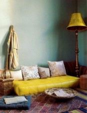 a colorful Moroccan living room with green walls, a yellow sofa and bold rugs and a traditional lantern